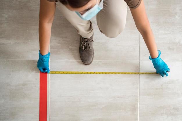 Donna che mette nastro adesivo sul pavimento per allontanamento sociale con misuratore di nastro