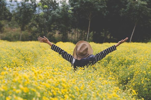 La donna alza la mano nel campo di fiori di crisantemo giallo, sentendosi felice e libera