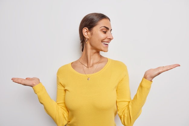 La donna alza i palmi sceglie tra due opzioni finge di tenere qualcosa indossa un maglione giallo casual su bianco