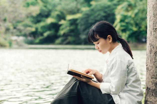 Donna che legge la bibbia al mattino sullo sfondo della natura. concetto di fede, spiritualità e religione