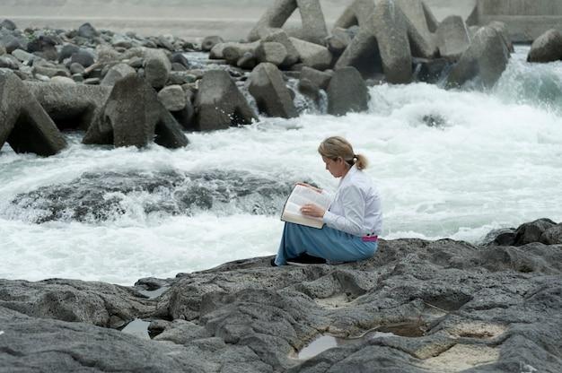 Donna che legge la bibbia seduto dal fiume fujikawa nella città di fuji, giappone.