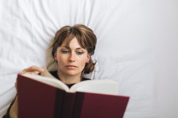 Donna che legge un libro su un letto durante la quarantena del coronavirus