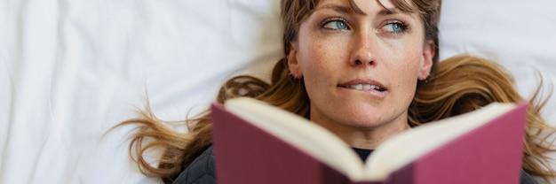 Donna che legge un libro a letto durante la quarantena del coronavirus