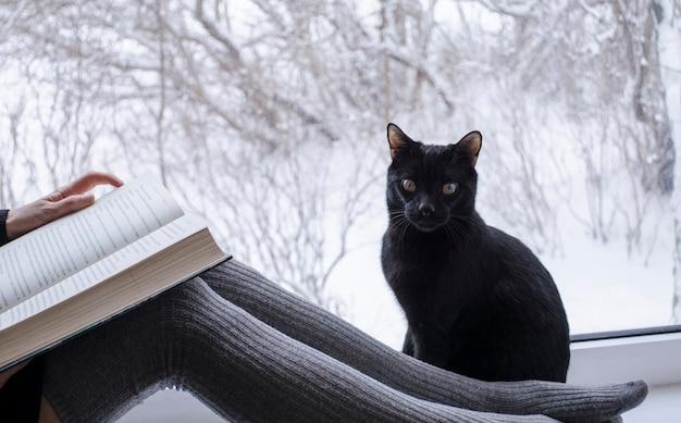 Donna che legge un libro accanto a un gatto nero