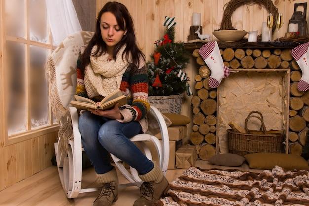 Donna che legge un libro sulla sedia accanto al mantello in una capanna rustica a natale