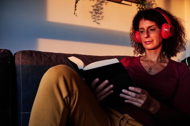Donna che legge un libro sul divano durante la quarantena per coronavirus - concetto di stare a casa
