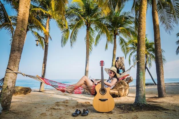 Una donna che legge un libro sull'amaca sotto il cocco durante le vacanze.