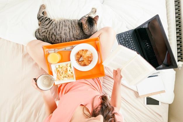 Donna che legge il libro e fa colazione. è nella sua camera da letto. vista dall'alto