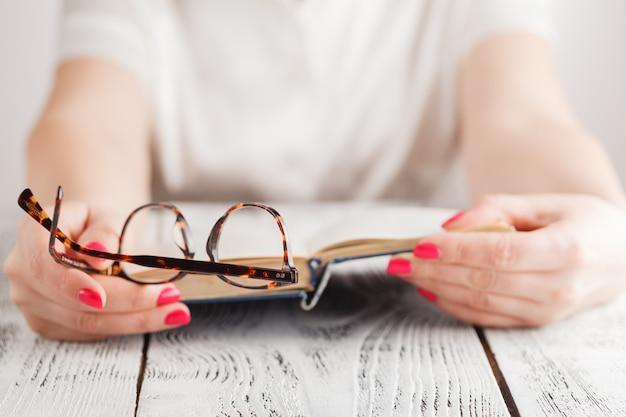 Donna che legge un libro e in mano tiene un paio di occhiali