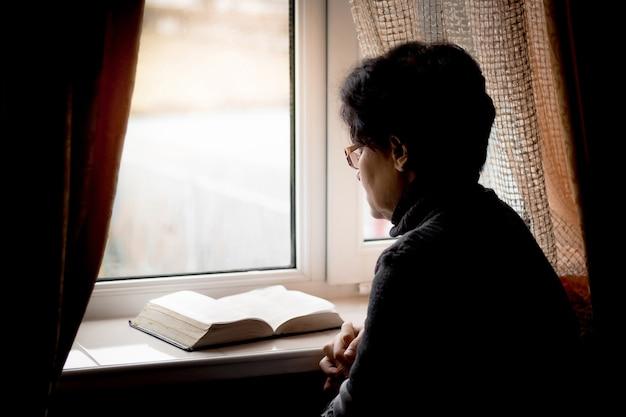 Libro di lettura della donna vicino a una finestra, donna che prega e che medita