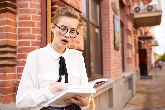 Libro di lettura della donna sulla strada vicino alla costruzione di mattoni e studente di scienze dell'educazione del taccuino