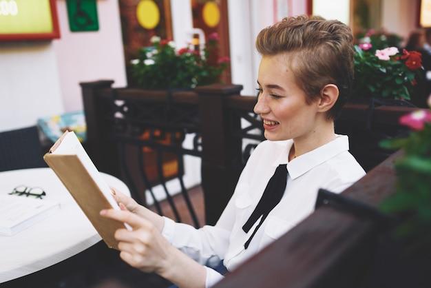 Donna che legge un libro a un tavolo in un blocco note di caffè studentessa jeans scarpe da ginnastica camicia
