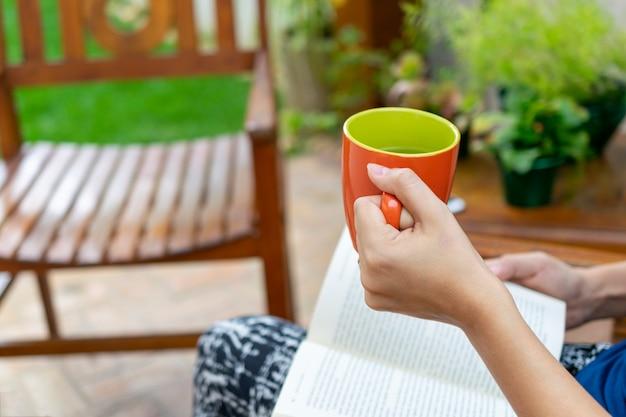 Libro di lettura della donna con la tazza di tè a disposizione. concetto di lettura e relax.