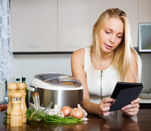 Donna che legge l'ereader e cucina con crockpot