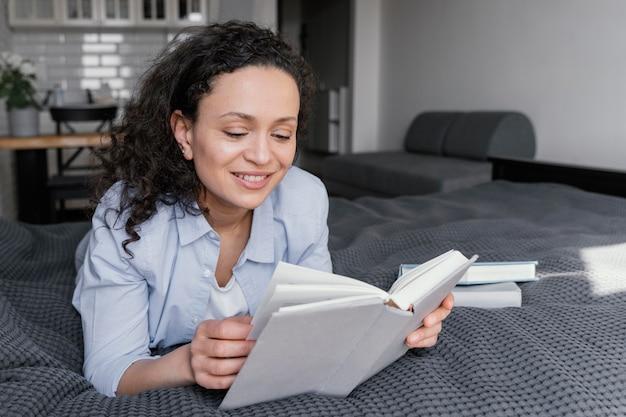 Donna che legge in casa pieno colpo