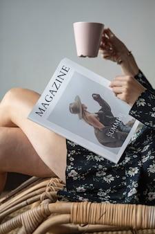 Donna che legge una rivista con una tazza di caffè