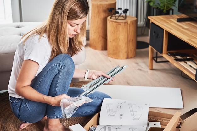 Donna che legge il manuale di istruzioni per montare i mobili