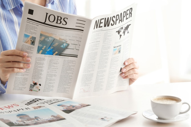 Donna che legge il giornale del mattino al chiuso