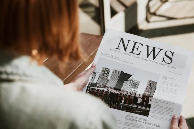 Donna che legge un giornale in un bar