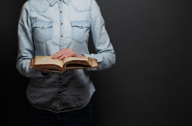 Donna che legge una vecchia bibbia su uno sfondo grigio