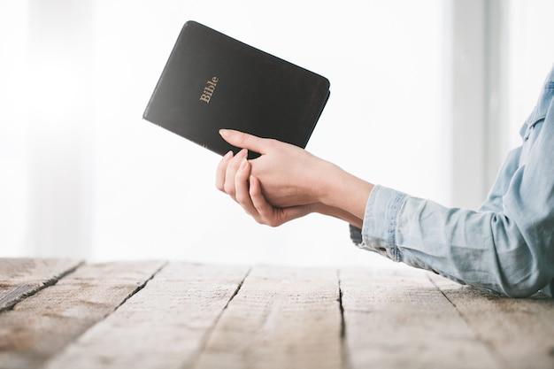 Donna che legge e prega sulla bibbia
