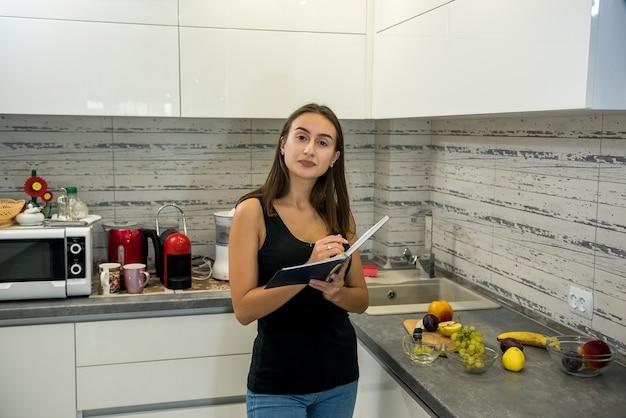 Donna legge un taccuino in cucina per cucinare cibi sani
