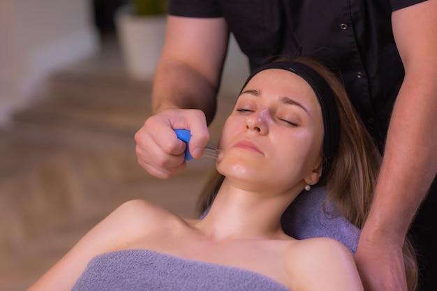 La donna riceve il massaggio facciale con coppettazione ringiovanimento del viso presso il centro benessere di agopuntura.