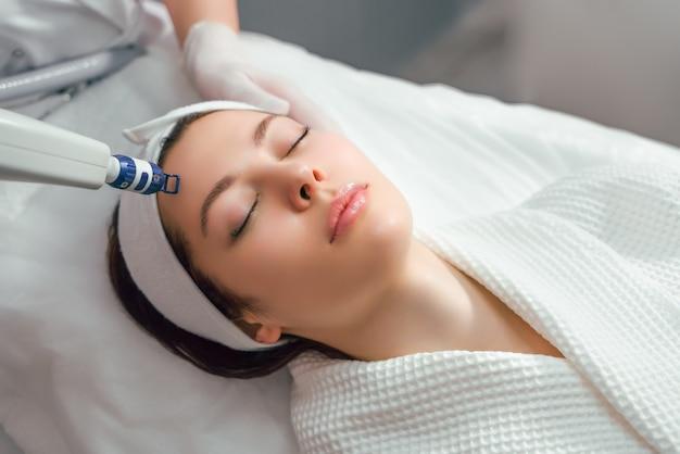 Una donna riceve un trattamento laser del viso in una clinica di cosmetologia un concetto di ringiovanimento della pelle