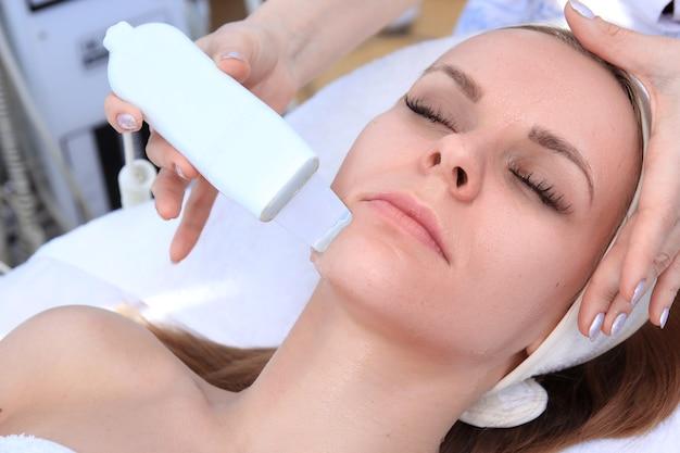 Donna che riceve la terapia di pulizia con un'apparecchiatura ad ultrasuoni professionale in ufficio di cosmetologia