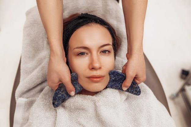 Donna che riceve il massaggio del viso nel salone di bellezza.
