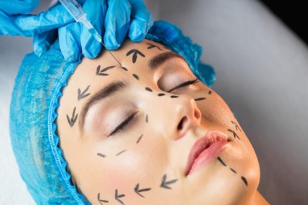 Donna che riceve l'iniezione sulla sua fronte