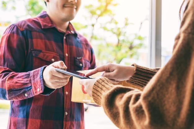 Donna che riceve la cassetta dei pacchi e firma il nome al telefono dal fattorino alla porta di casa
