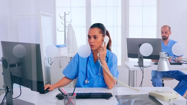 Receptionist donna che risponde al telefono, lavora in clinica ospedaliera scrivendo sul computer, fissando appuntamenti. medico in uniforme che scrive un elenco di pazienti consultati e diagnosticati, effettuando ricerche.