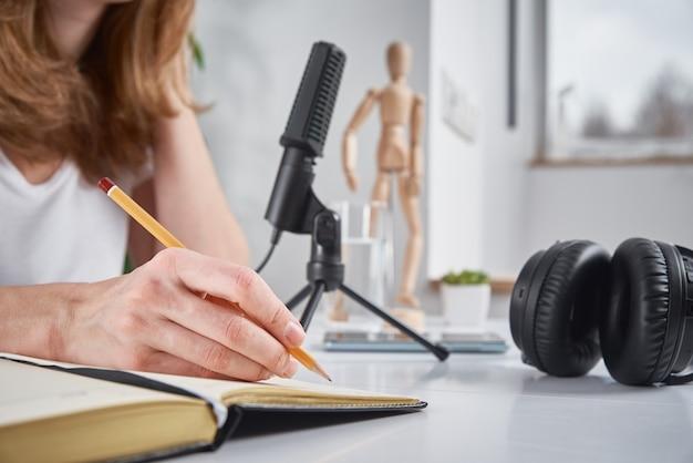 Donna che registra podcast in linea a casa, concetto di podcasting