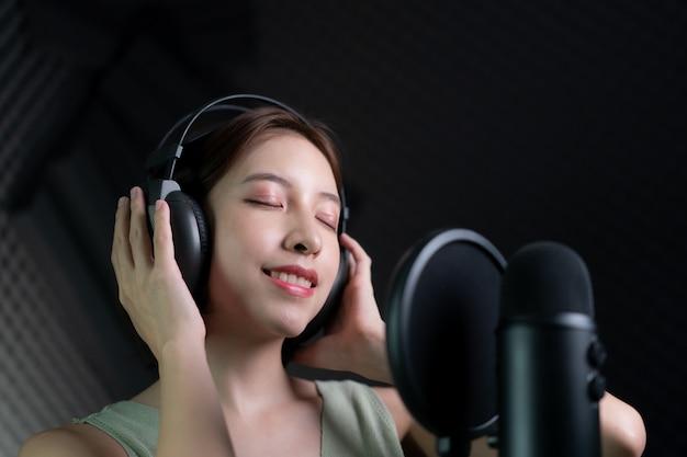 Donna che registra una canzone o una narrazione in studio