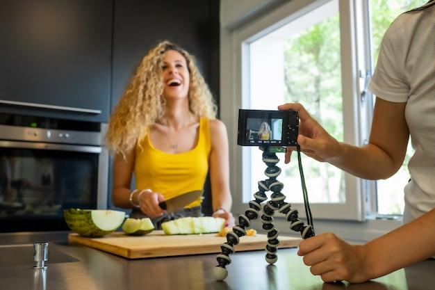 La registrazione della donna con una macchina fotografica gradisce una taglierina del melone in una cucina