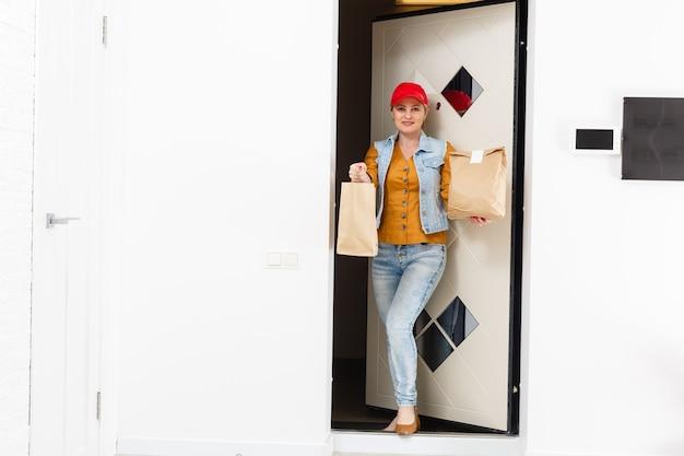 Donna in berretto rosso che dà priorità bassa domestica di ordine degli alimenti a rapida preparazione. corriere femminile che tiene pacchetto di carta con cibo. consegna prodotti da negozio o ristorante a casa. copia spazio