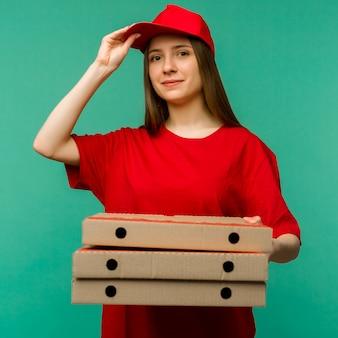 Donna in berretto rosso, t-shirt che dà le scatole di pizza di ordine alimentare sull'azzurro.