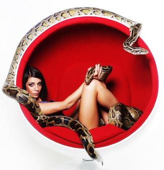 Donna in pitone rosso sedia holdung