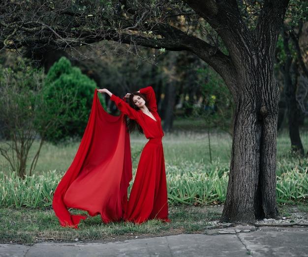 Donna in abito rosso che basa lo stile di vita della natura summer