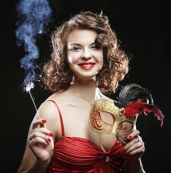 Donna in abito rosso al carnevale con maschera, flute da champagne e luce bengala