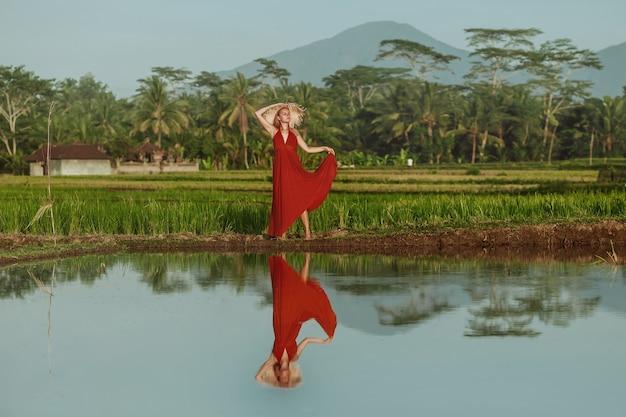 Una donna con un vestito rosso e un cappello cammina nelle risaie di bali
