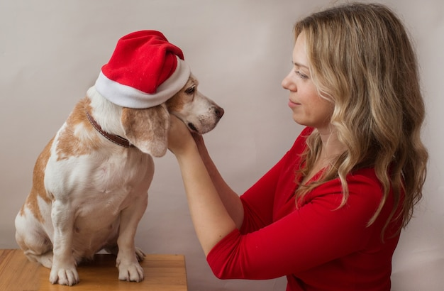 Donna in vestito rosso che tiene beagle in santa hat indoor. migliori amici consept.