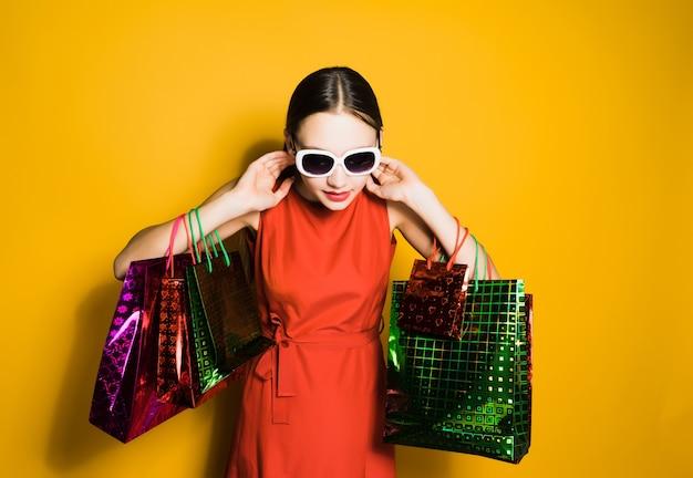 Donna in vestito rosso che tiene le borse della spesa