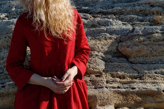 Una donna con un vestito rosso è in piedi sulla spiaggia.