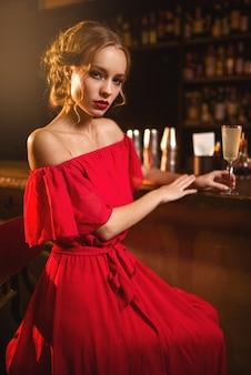 Donna in abito rosso in piedi al bancone del bar