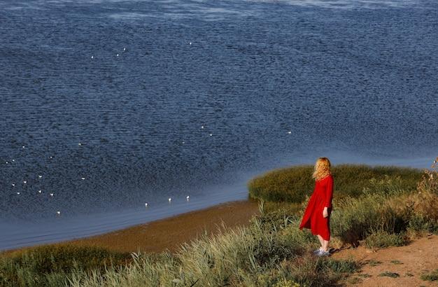 La donna in vestito rosso cammina lungo la riva del mare all'alba.