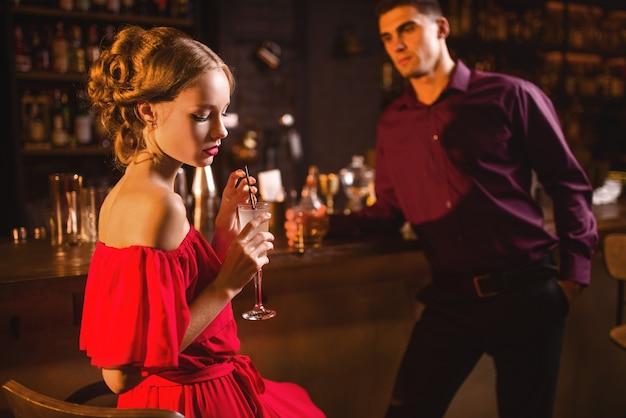 Donna in abito rosso con cocktail in mano, flirtare