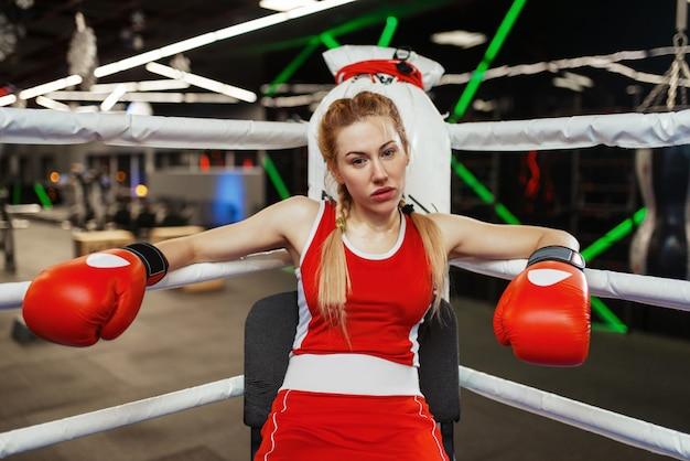 Donna in guanti rossi che si siede nell'angolo del ring di pugilato, allenamento di box.