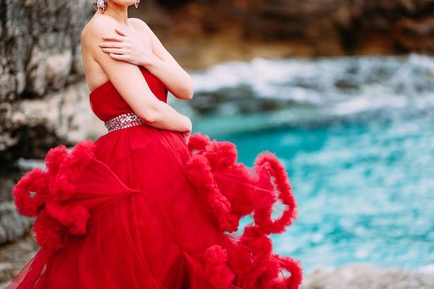 Donna in un abito rosso che si abbraccia su una spiaggia rocciosa